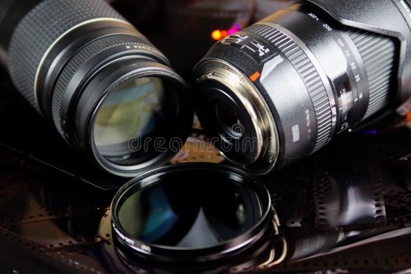 Ciérrese para arriba de dos lentes de cámara con el filtro circular aislado en tiras de la película negativa fotos de archivo