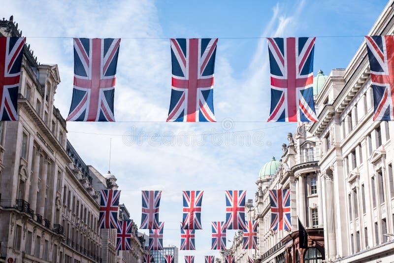 Ciérrese para arriba de edificios en Regent Street London con la fila de banderas británicas para celebrar la boda de príncipe Ha imágenes de archivo libres de regalías