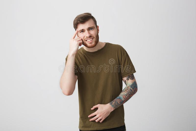 Ciérrese para arriba de estudiante masculino tatuado barbudo hermoso joven infeliz con el pelo oscuro corto en la camisa marrón q fotografía de archivo
