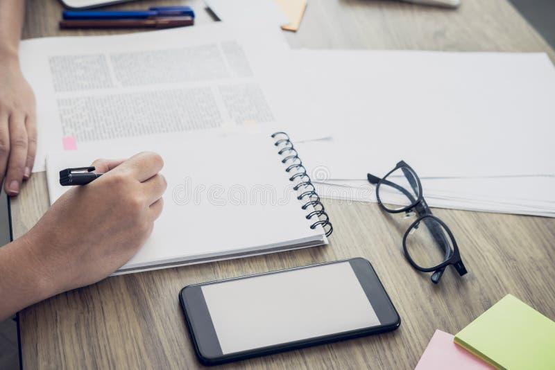 Ciérrese para arriba de estudiar las manos del estudiante que escriben en libro durante lectur fotografía de archivo libre de regalías