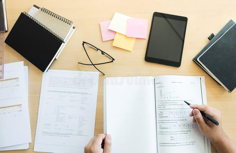 Ciérrese para arriba de estudiar las manos del estudiante que escriben en libro durante lectur foto de archivo libre de regalías
