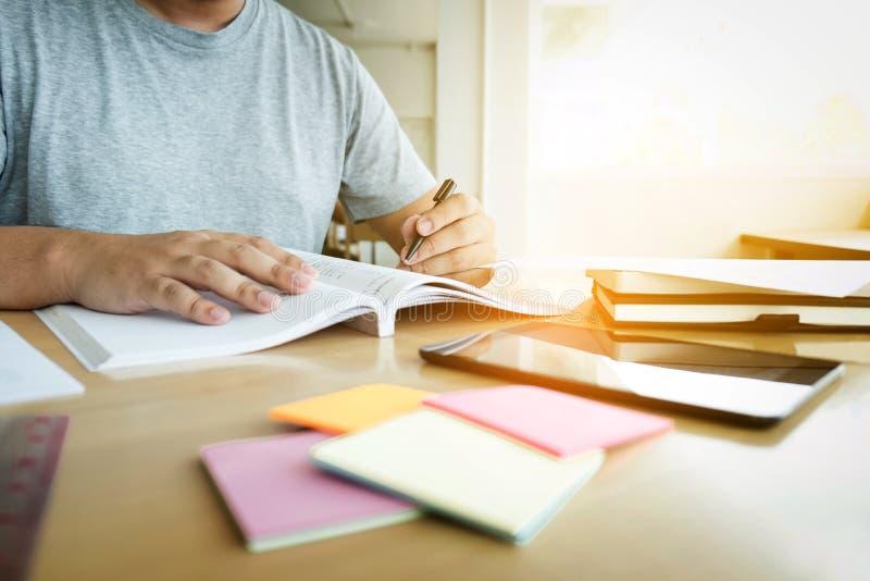 Ciérrese para arriba de estudiar las manos del estudiante que escriben en libro durante lectur imagen de archivo