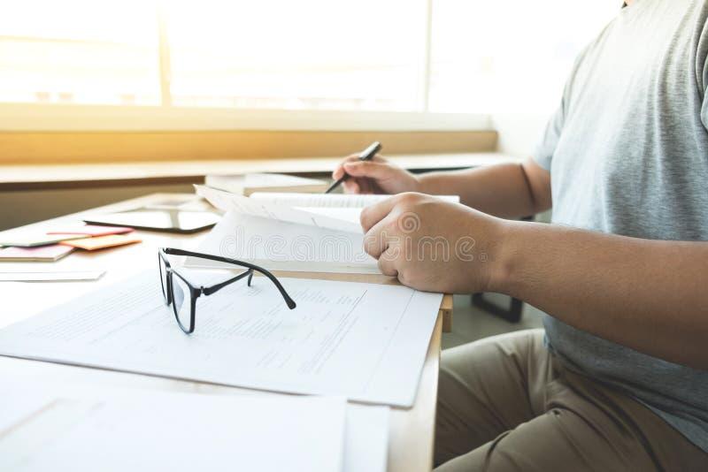 Ciérrese para arriba de estudiar las manos del estudiante que escriben en libro durante lectur fotos de archivo