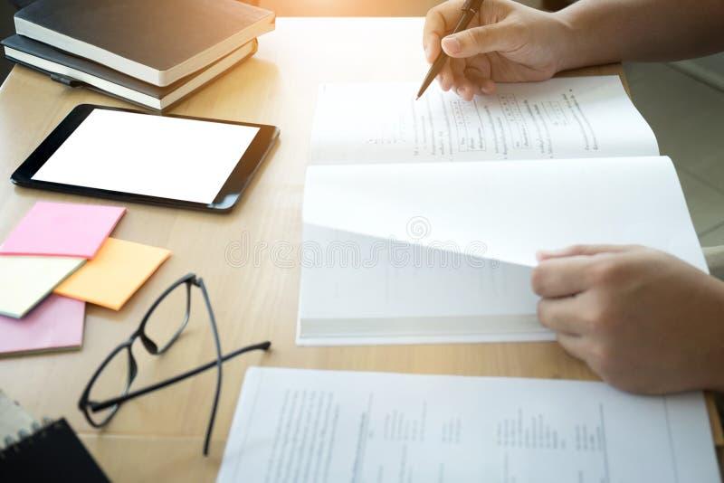 Ciérrese para arriba de estudiar las manos del estudiante que escriben en libro durante lectur imagen de archivo libre de regalías