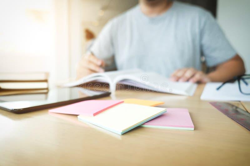 Ciérrese para arriba de estudiar las manos del estudiante que escriben en libro durante lectur fotografía de archivo