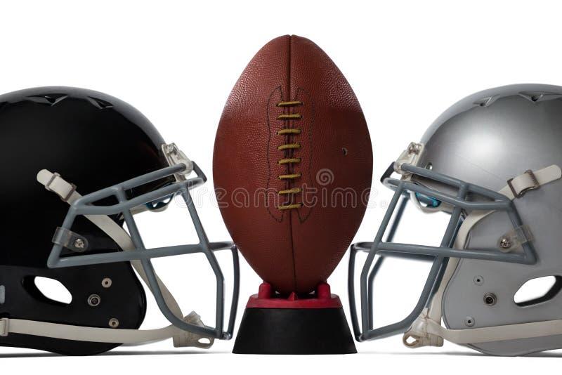 Ciérrese para arriba de fútbol americano marrón en camiseta por los cascos de los deportes imagen de archivo
