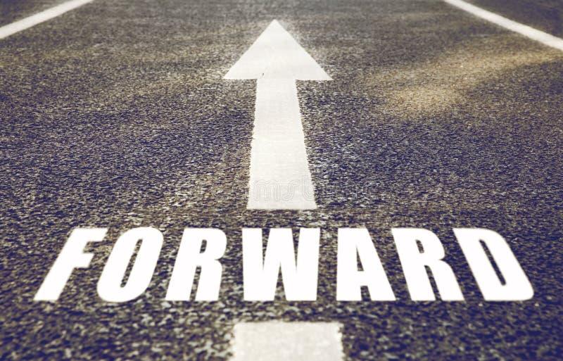 Ciérrese para arriba de flecha y redacte adelante en la carretera de asfalto imagen de archivo libre de regalías