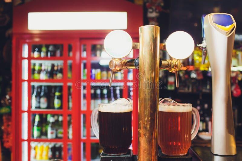 Ciérrese para arriba de golpecitos de la cerveza en fila Equipo metálico para las barras y los mini brewerys Concepto de equipo m imagen de archivo libre de regalías