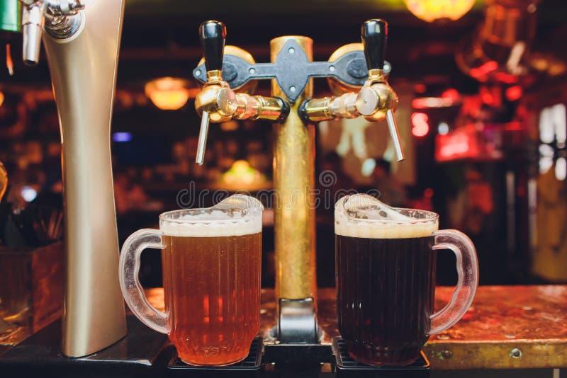 Ciérrese para arriba de golpecitos de la cerveza en fila Equipo metálico para las barras y los mini brewerys Concepto de equipo m imagenes de archivo