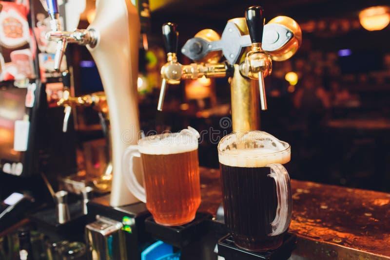 Ciérrese para arriba de golpecitos de la cerveza en fila Equipo metálico para las barras y los mini brewerys Concepto de equipo m fotos de archivo libres de regalías