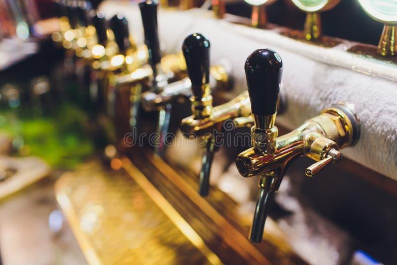 Ciérrese para arriba de golpecitos de la cerveza en fila Equipo metálico para las barras y los mini brewerys Concepto de equipo m foto de archivo
