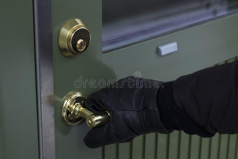 Ciérrese para arriba de guantes negros en el tirador de puerta de la seguridad - Ladrón - imagen de adaptación del concepto fotos de archivo libres de regalías