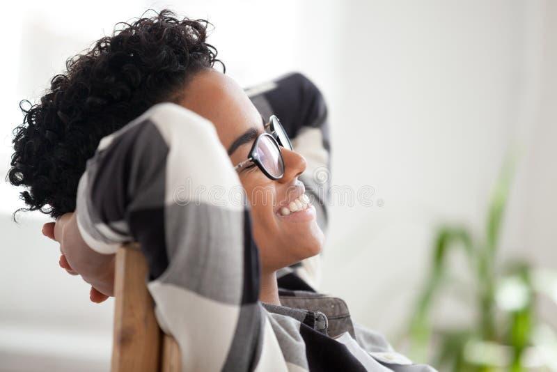 Ciérrese para arriba de hembra negra feliz se relajan en la sonrisa de la silla foto de archivo libre de regalías