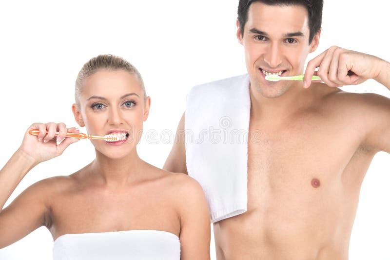 Ciérrese para arriba de hombre atractivo del ajuste y de los dientes de cepillado de la mujer con los cepillos de dientes imágenes de archivo libres de regalías