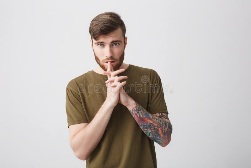 Ciérrese para arriba de hombre barbudo atractivo apuesto joven con el pelo corto oscuro y el brazo tatuado en la tenencia brillan imagen de archivo
