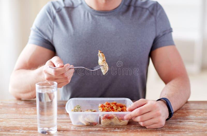 Ciérrese para arriba de hombre con la bifurcación y riegue la consumición de la comida foto de archivo
