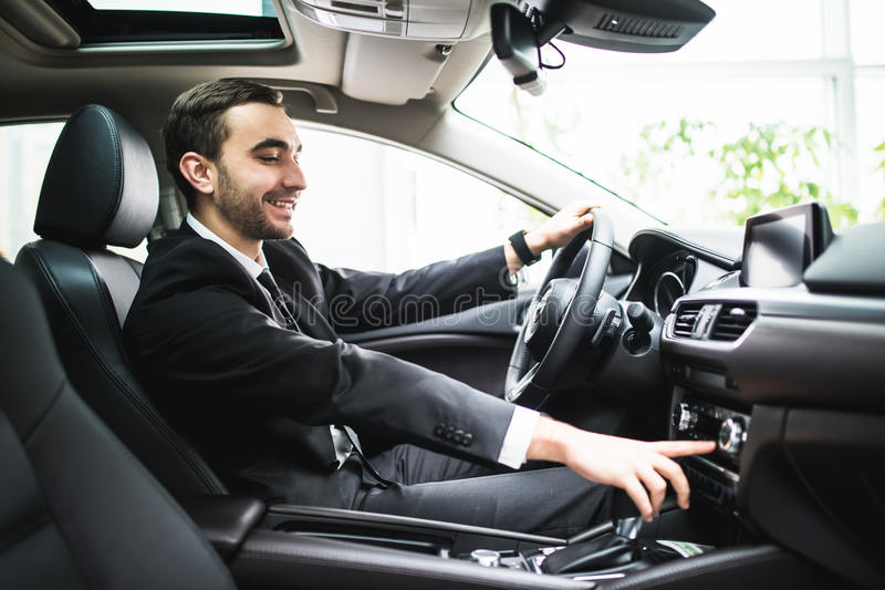 Ciérrese para arriba de hombre joven en el traje que conduce el coche y que cambia un poco de botón en el panel del coche fotos de archivo