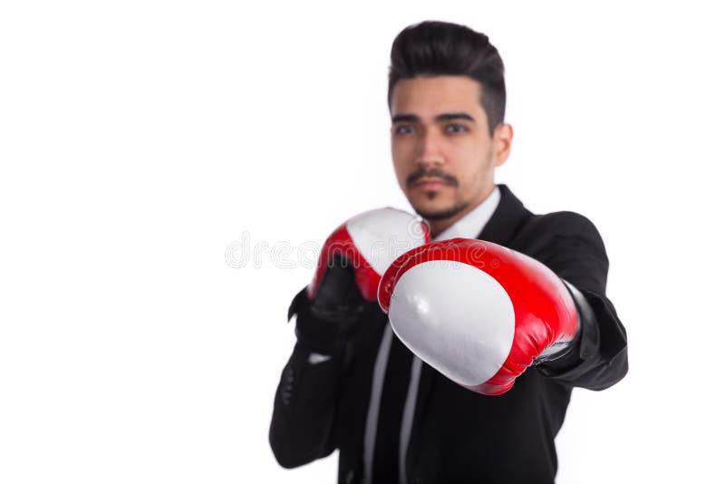 Ciérrese para arriba de hombre de negocios acertado en traje negro y guantes de boxeo rojos imagen de archivo libre de regalías