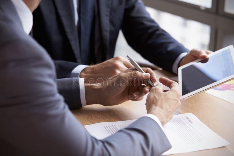 Ciérrese para arriba de hombres de negocios usando la tableta de Digitaces en la reunión foto de archivo libre de regalías
