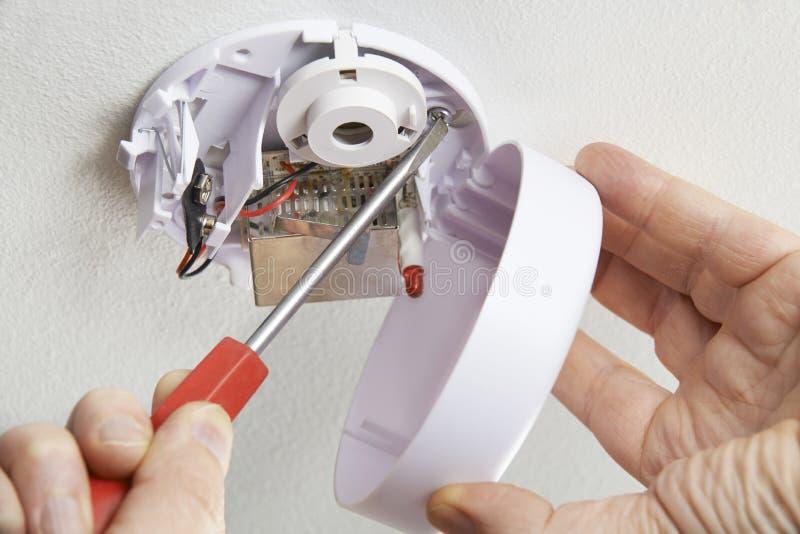 Ciérrese para arriba de instalar el detector de humo en casa fotografía de archivo
