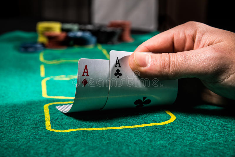 Ciérrese para arriba de jugador de póker con dos naipes y microprocesadores de los as en la tabla verde del casino imágenes de archivo libres de regalías