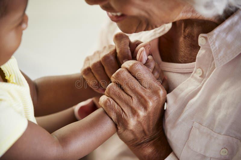 Ciérrese para arriba de la abuela que lleva a cabo las manos con la nieta del bebé que juega al juego junto imagenes de archivo