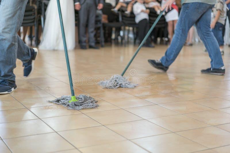Ciérrese para arriba de la acción de limpieza del piso con el limpiador Concepto de la limpieza y de la limpieza Foco seleccionad fotos de archivo