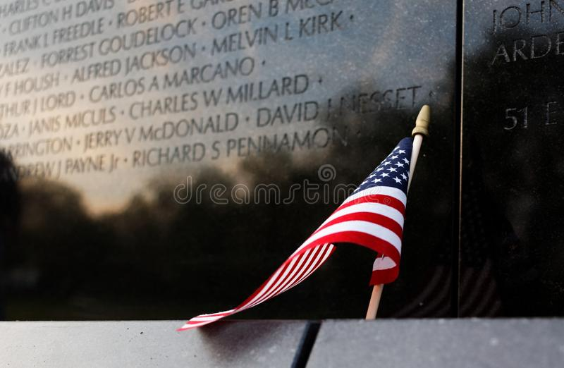 Ciérrese para arriba de la bandera americana que se inclina contra el monumento de guerra de Vietnam, Washington DC, los E.E.U.U. fotografía de archivo