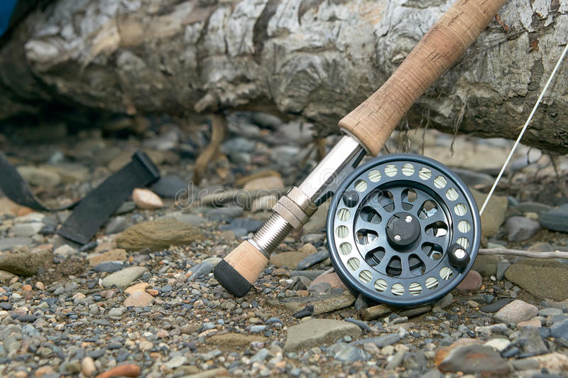 Ciérrese para arriba de la barra y del carrete de pesca con mosca en riverbank fotografía de archivo libre de regalías