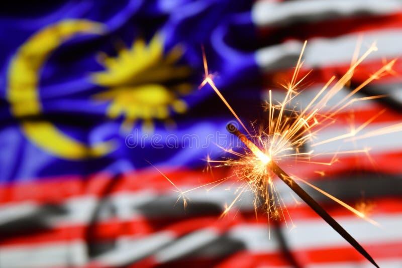 Ciérrese para arriba de la bengala que quema sobre la bandera de Malasia Días de fiesta, celebración, concepto del partido foto de archivo