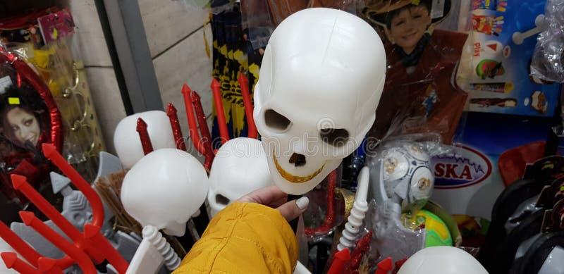 Ciérrese para arriba de la cabeza intrépida blanca del scull en la mano femenina expuesta en venta en una tienda antes de pur jud foto de archivo