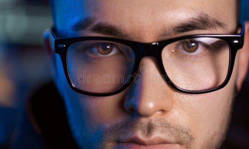 Ciérrese para arriba de la cara del pirata informático asiático del varón en vidrios imagen de archivo