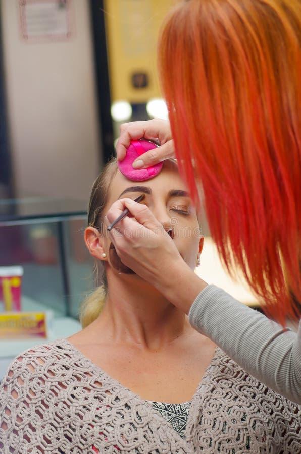Ciérrese para arriba de la cara hermosa de la mujer joven que consigue maquillaje El artista está aplicando el rimel del ojo en e imágenes de archivo libres de regalías