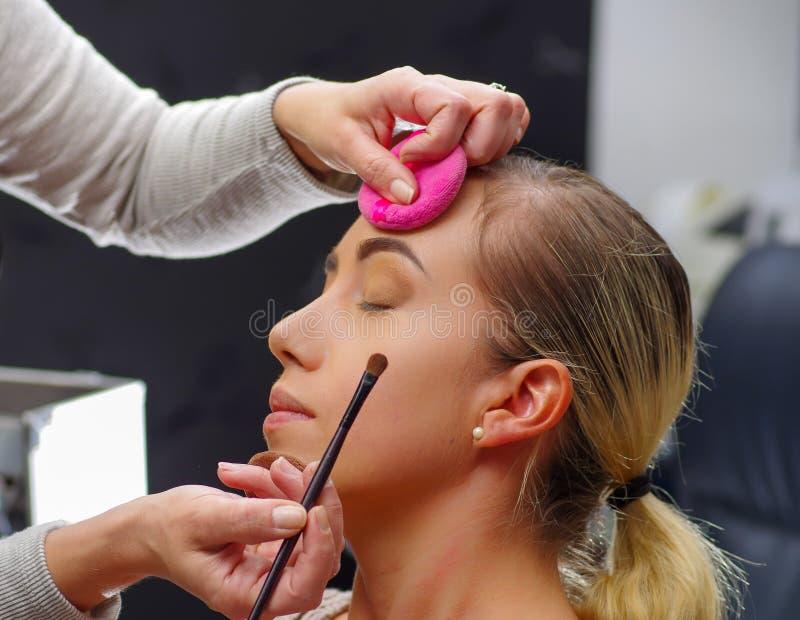 Ciérrese para arriba de la cara hermosa de la mujer joven que consigue maquillaje, usando un cepillo, los ojos cerrados señora co fotografía de archivo