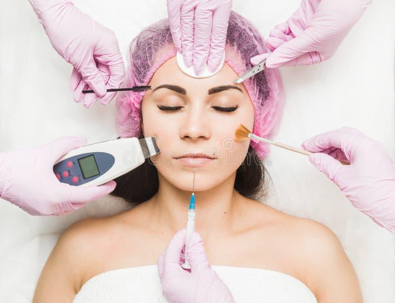 Ciérrese para arriba de la cara hermosa de una mujer joven Muchas manos que sostienen las herramientas de la cosmetología cerca d foto de archivo libre de regalías
