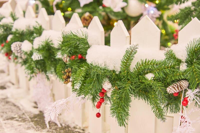 Ciérrese para arriba de la cerca blanca adornada con la guirnalda de la Navidad con los conos y la nieve Decoración festiva del p foto de archivo
