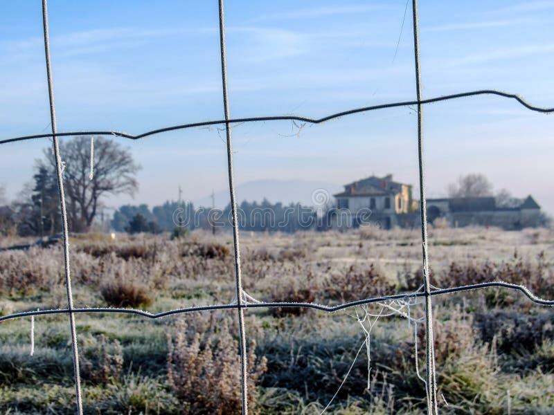 Ciérrese para arriba de la cerca helada de la malla metálica y de la casa francesa vieja típica en el fondo fotos de archivo libres de regalías