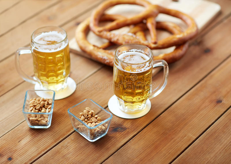 Ciérrese para arriba de la cerveza, de los pretzeles y de los cacahuetes en la tabla foto de archivo