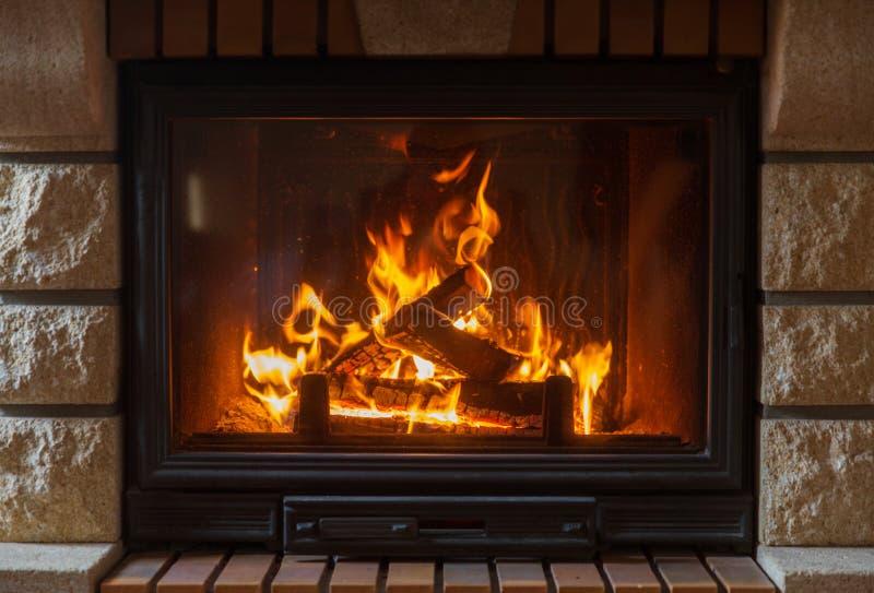 Ciérrese para arriba de la chimenea ardiente en casa imagen de archivo libre de regalías