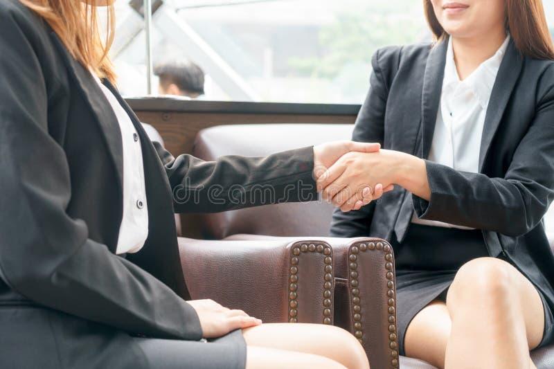 Ciérrese para arriba de la empresaria de dos sonrisas que sacude las manos mientras que se sienta fotografía de archivo libre de regalías