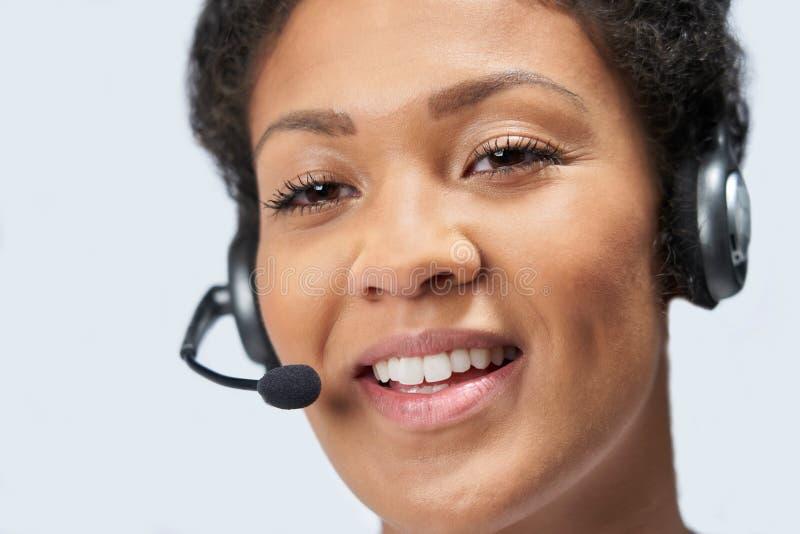 Ciérrese para arriba de la empresaria Wearing Telephone Headset en el departamento de servicios de atención al cliente fotografía de archivo libre de regalías