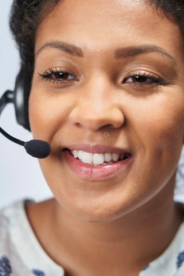 Ciérrese para arriba de la empresaria Wearing Telephone Headset en el departamento de servicios de atención al cliente foto de archivo