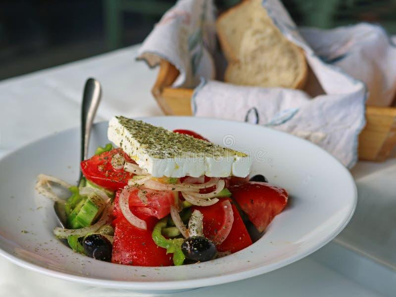 Ciérrese para arriba de la ensalada griega con los tomates frescos, las cebollas, el queso feta y las aceitunas negras imagen de archivo