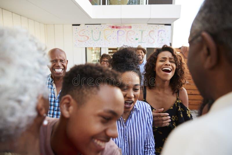 Ciérrese para arriba de la familia afroamericana que acoge con satisfacción a abuelos a casa para un partido de sorpresa fotos de archivo