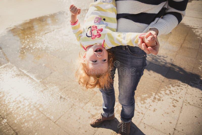 Ciérrese para arriba de la familia cariñosa alegre feliz, de la madre y de la pequeña hija jugando en parque al lado de la fuente foto de archivo libre de regalías