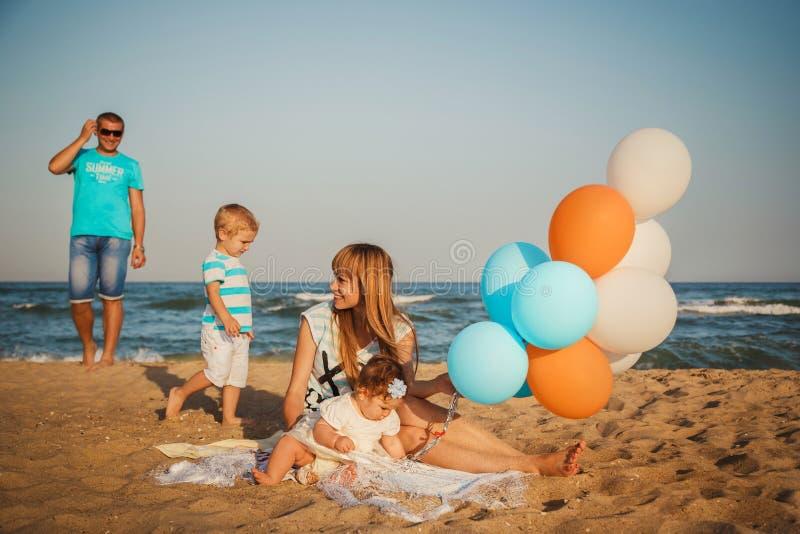 Ciérrese para arriba de la familia cariñosa feliz joven con los pequeños niños, divirtiéndose en la playa junto cerca del océano, foto de archivo