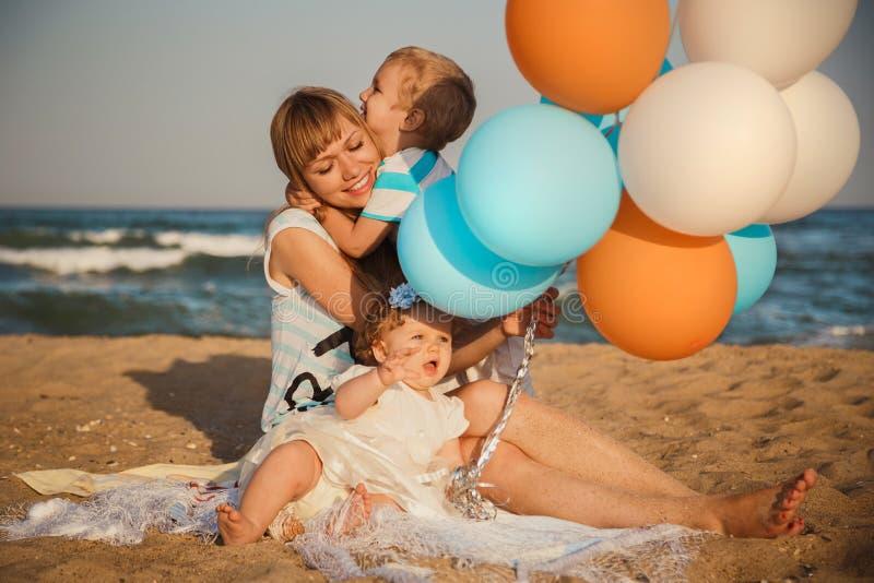 Ciérrese para arriba de la familia cariñosa feliz joven con los pequeños niños, divirtiéndose en la playa junto cerca del océano, imagen de archivo