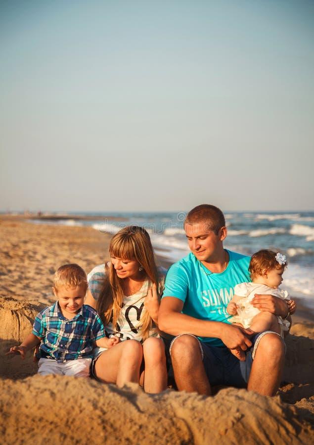 Ciérrese para arriba de la familia cariñosa feliz joven con los pequeños niños, divirtiéndose en la playa junto cerca del océano, fotos de archivo