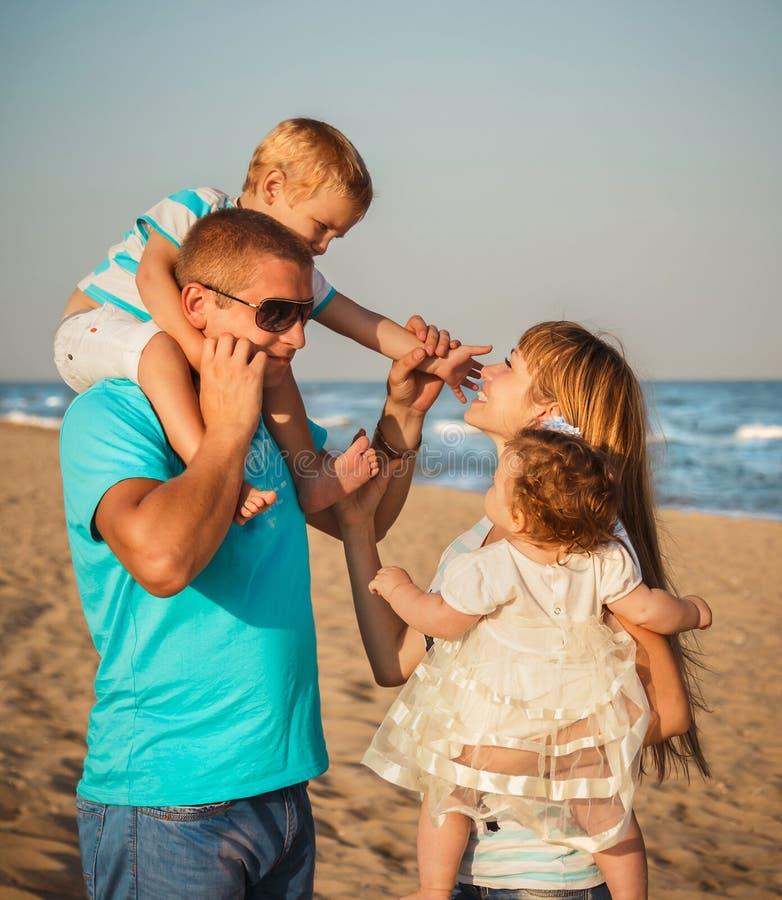 Ciérrese para arriba de la familia cariñosa feliz joven que abraza en la playa junto cerca del océano, concepto de familia feliz  imagenes de archivo
