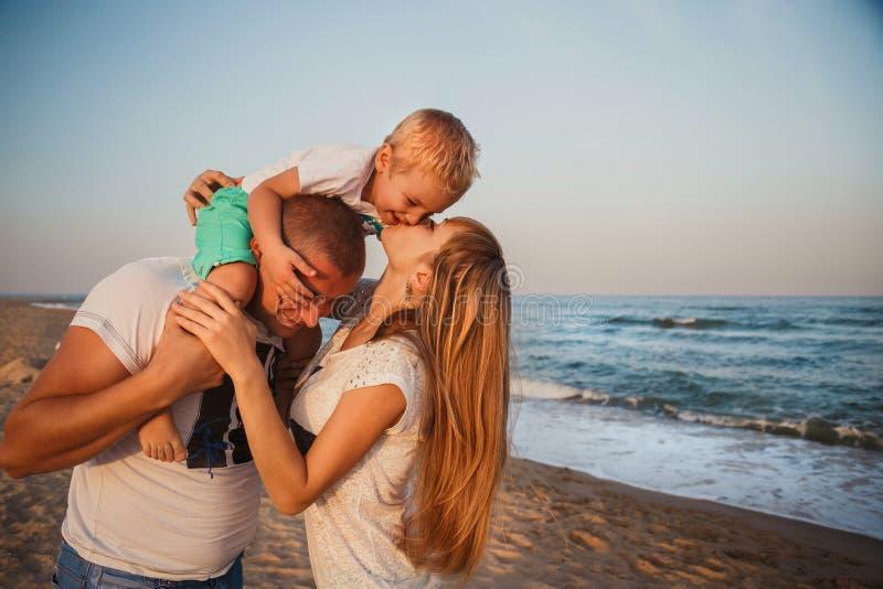 Ciérrese para arriba de la familia cariñosa feliz joven que abraza en la playa junto cerca del océano, concepto de familia feliz  imagen de archivo libre de regalías